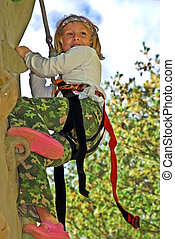 Girl on Climbing Wall - A cute girl smiling as she ascends a...