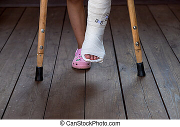 Girl on crutches, leg in cast. patient holding wooden crutches isolated on blurred background. kid after misadventure , insurance concept. difficulties of movement. Copy space