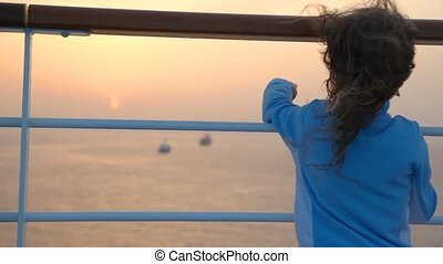 girl on deck looks at ships in sea