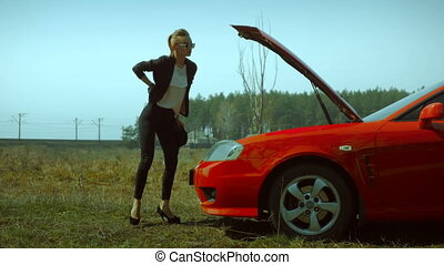 girl on high heels looks under the hood of the sports
