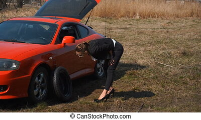girl on high heels trying to change the punctured wheel car...