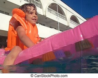 girl on inflatable mattress in swimming pool