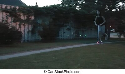 Girl on Ligted Scooter at Night