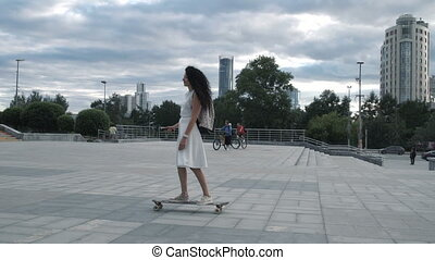 Girl on longboard riding at street