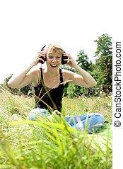 girl on meadow with headphones