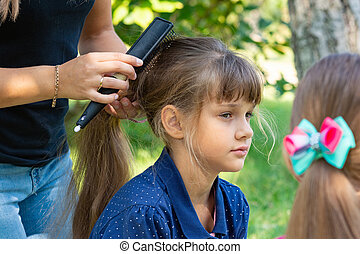 Girl on nature combs her hair with a girl
