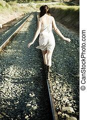 Young unrecognizable girl walking on railway