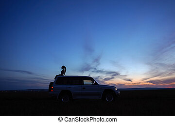 Girl on roof of car on background of sunset sky