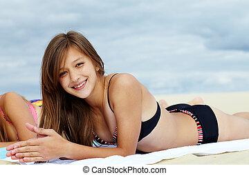 Girl on sand - Portrait of teenage girl in bikini sunbathing...