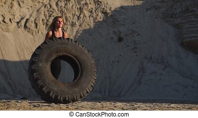 Girl on sand quarry pushing wheel in training crossfit workout.