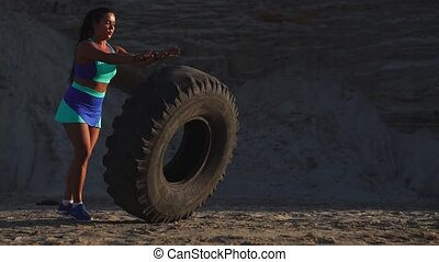 Girl on sand quarry pushing wheel in training crossfit workout