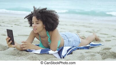 Girl on sandy shoreline taking selfie - Young fit black girl...