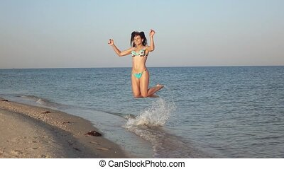 Girl on sea shoal jumps - Young girl on the sandy plait of...