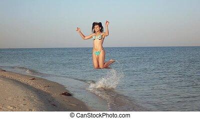 Girl on sea shoal jumps
