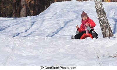 A little girl driving in a sledge