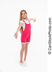 Girl on smiling face posing in pink overalls, isolated on white background. Kid girl with long hair wears cute clothing. Teens fashion concept. Girl likes to look cute, stylish and fashionable