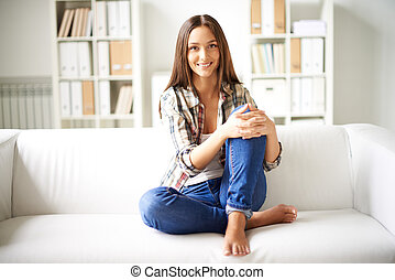 Girl on sofa - Happy girl in casual clothes sitting on sofa