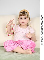 girl on  sofa in  eastern hat with beads