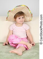 girl on sofa in straw hat