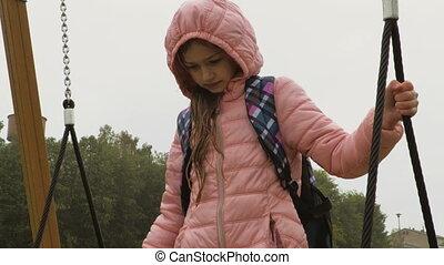 Girl on Swings in rainy day