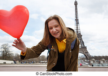 girl with a balloon in the shape of a hearton the background of the Eiffel Tower in Paris. France