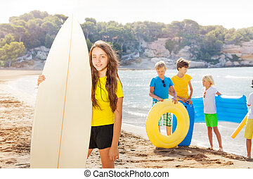 Girl on the beach standing with surf board