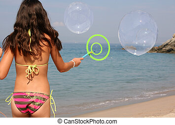 Girl on the beach - Teen girl playing with bubbles on the ...