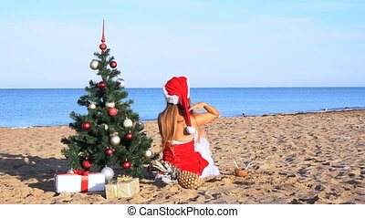 girl on the beach under the Christmas tree for Christmas in the tropics