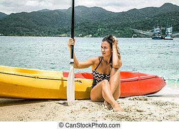 girl on the beach with a canoe