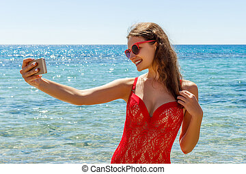 Girl on the beach with a cell phone making selfie on sunny day