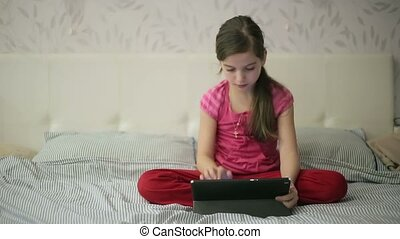 Girl on the bed educations on tablet