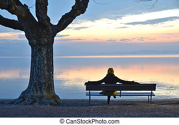 Girl on the bench against lake of Zug, Switzerland