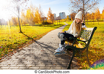 Girl on the bench with roller blades