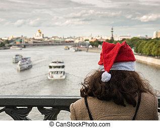Girl on the bridge in Santa's hat
