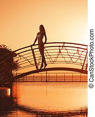 Girl on the bridge over a pool