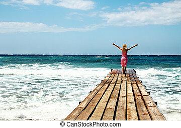 Girl on the bridge pier seashore