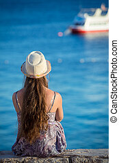 girl on the coast looking to the boat at sea