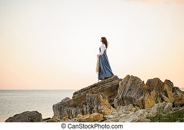 girl on the edge of a cliff looking out to sea