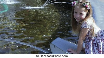 Girl on the edge of the fountain - In a beautiful dress the...