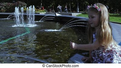 In a beautiful dress the girl on the edge of the fountain plays with a stream of water. Papa supports her