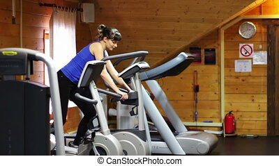 Girl on the fitness trainer at the gym.