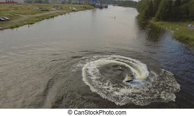 Girl on the jet ski in the river.Aerial video. - Girl riding...