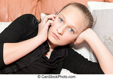 girl on the phone lying on a sofa