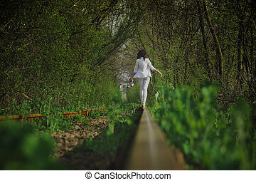 photo of a girl running away on the rails in nature