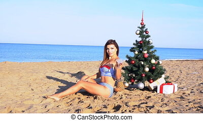 girl on the resort to the new year with a Christmas tree on the sea
