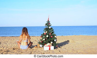 girl on the resort to the new year with a Christmas tree on...