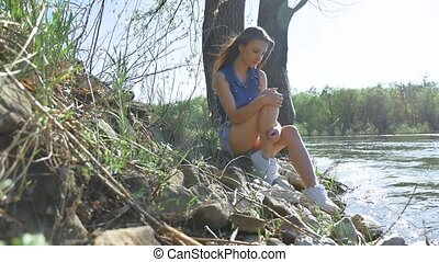 Girl on the river bank. Woman lifestyle sits by the water...