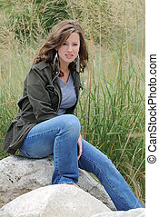Girl On The Rocks - A girl sitting in a field of grass on ...