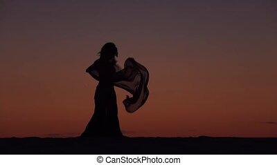Girl on the seashore gracefully dances her body against the...