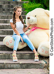 girl on the stairs in the park with a huge teddy bear posing
